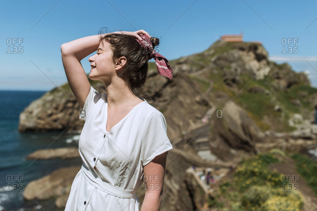 A young hippie girl poses in an island while observes the sea