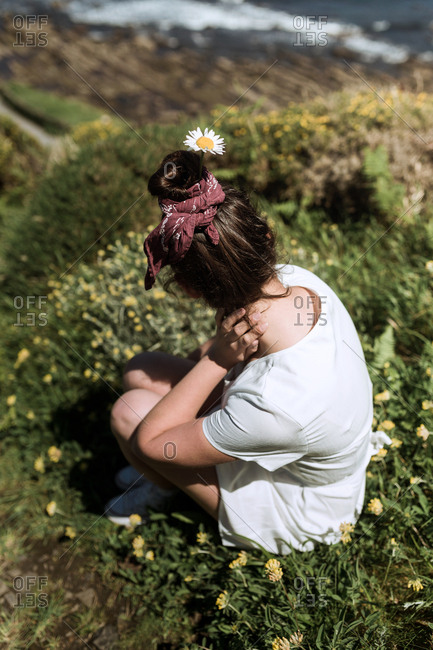 A young hippie girl observes the horizon in an island while hold a flower in her hair