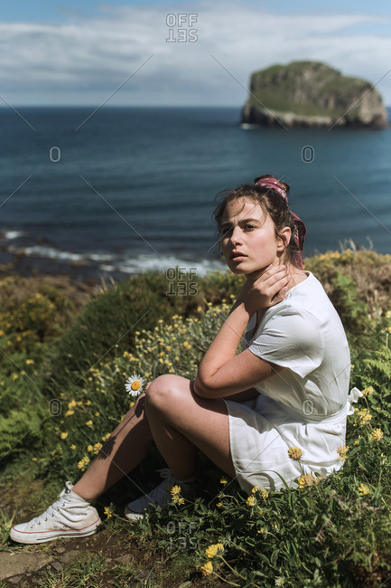 A young hippie girl observes the horizon in an island while hold a flower