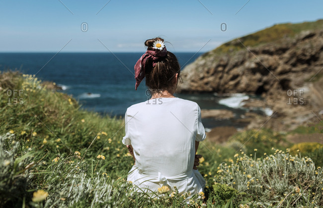 A young hippie girl observes the horizon in an island while hold a flower in her hat
