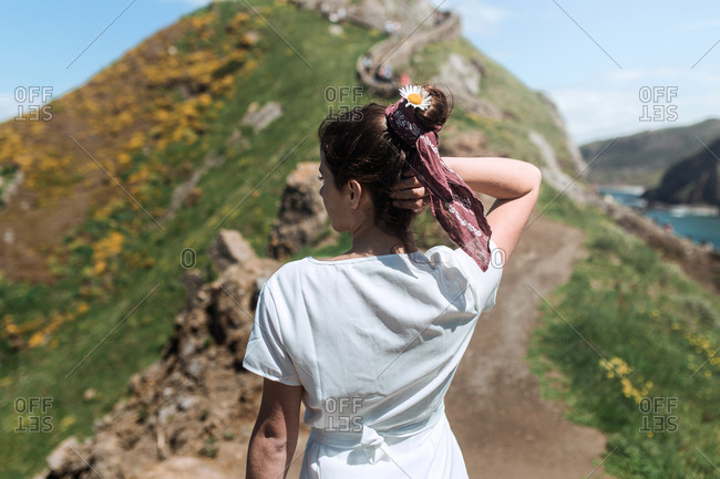 A young hippie girl touches her hair with a flower in her head