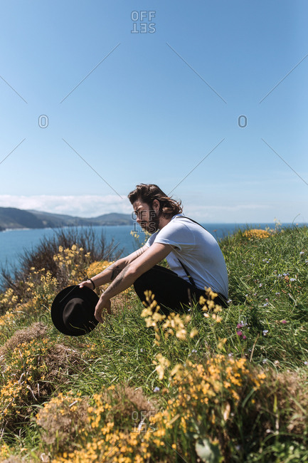 A young vintage man relaxes lying on an island in the middle of the flowers and glass