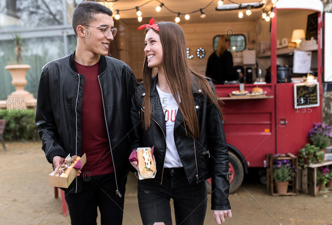 A young interracial couple walks on food truck festival while shares food