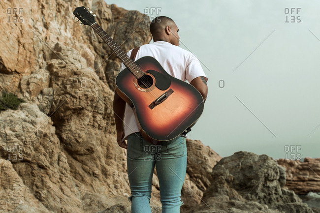 A boy with a guitar walks by the rocks on the beach