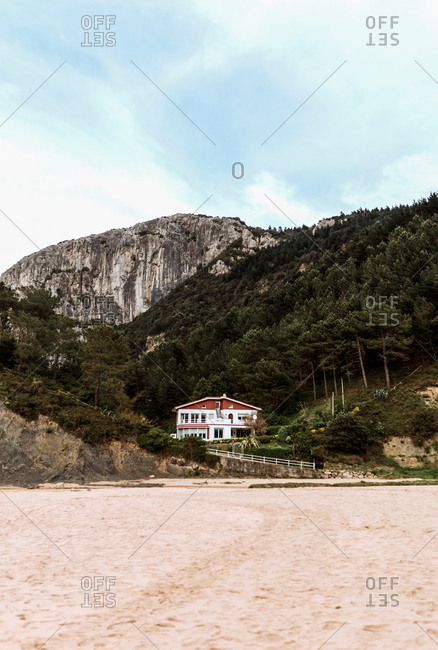 A house in the middle of the mountains on the beach