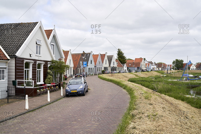 Amsterdam, Netherlands - May 18, 2018: Neighborhood with brick road and traditional houses in the village of Durgerdam