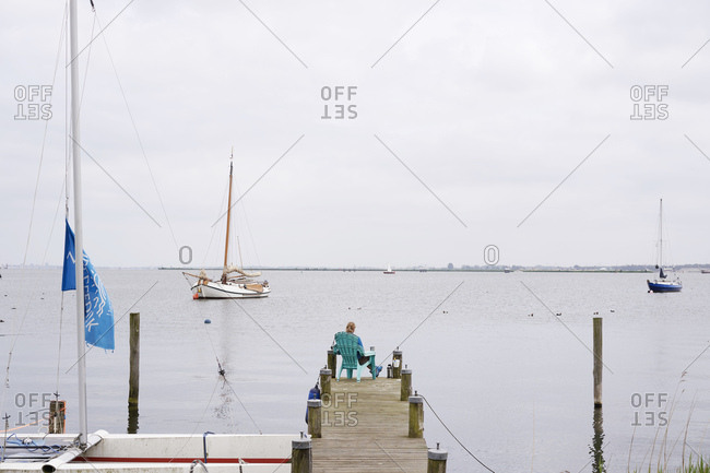 Amsterdam, Netherlands - May 18, 2018: Person sitting at the end of a dock in the village of Durgerdam