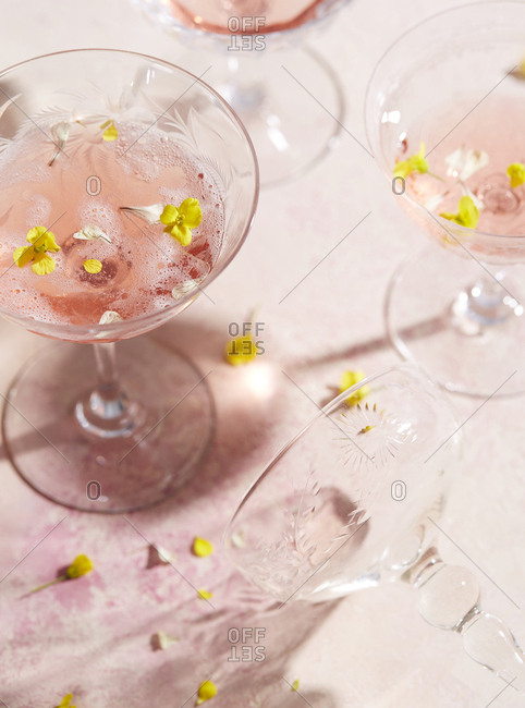 Overhead view of coupe glasses containing effervescent beverage garnished with flowers
