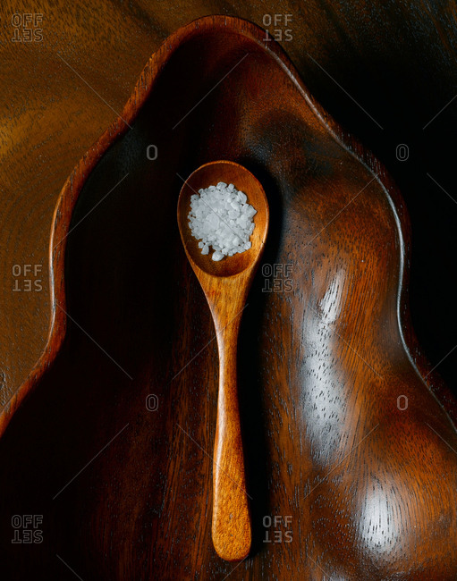 Top down view of coarse salt in wooden spoon arranged in leaf shaped wooden bowl