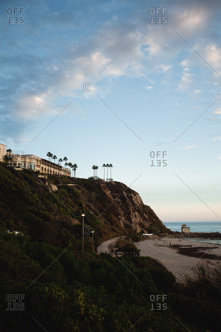 Luxury residence perched on cliff top looking out over ocean at sunset