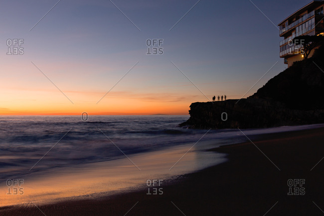 Group of people standing on rock below cliff top apartment building silhouetted against horizon at sunset