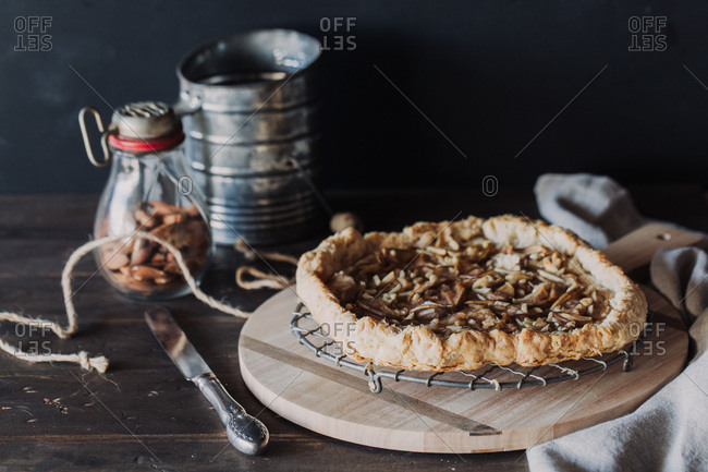High angle view of pie cooling on wire rack arranged with jar of almonds