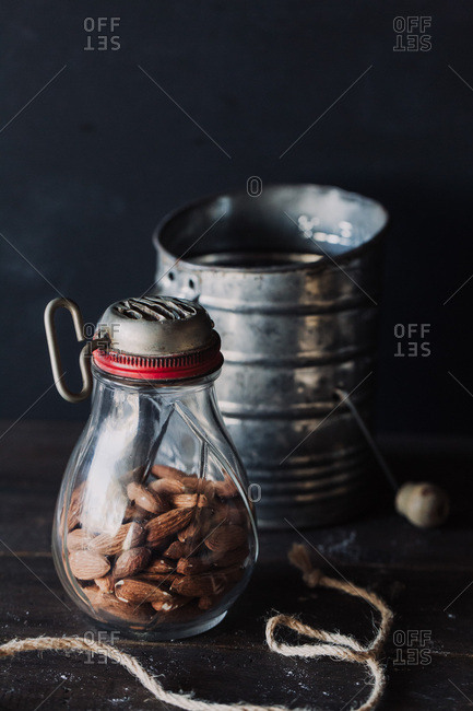 Almonds in antique glass grinder and tin can on dark table against dark background