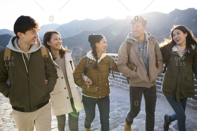 Happy young Chinese friends enjoying winter outing on the Great Wall