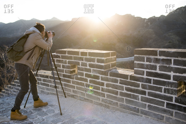 Young Chinese man photographing on the Great Wall