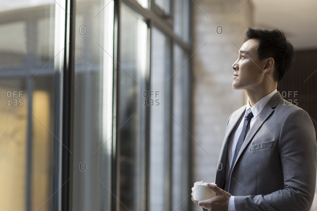 Confident Chinese businessman drinking coffee