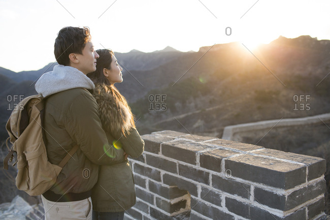 Happy young Chinese couple enjoying winter outing on the Great Wall