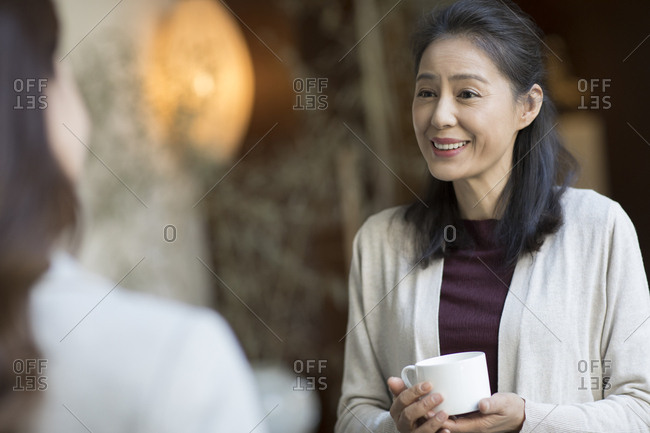 Elegance mature Chinese woman talking with young woman