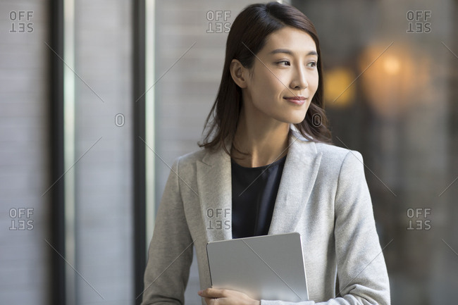 Young Chinese businesswoman holding a digital tablet