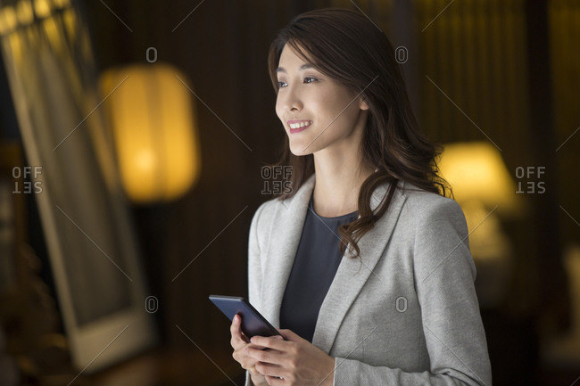 Cheerful young Chinese businesswoman holding a smart phone