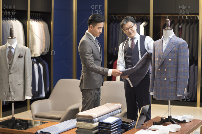 Chinese fashion designer and customer talking in menswear shop
