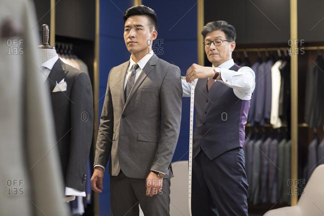 Chinese fashion designer taking measurement of customer