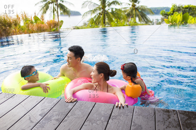 Happy young Chinese family having fun in swimming pool