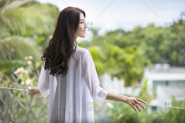 Happy young Chinese woman relaxing on balcony