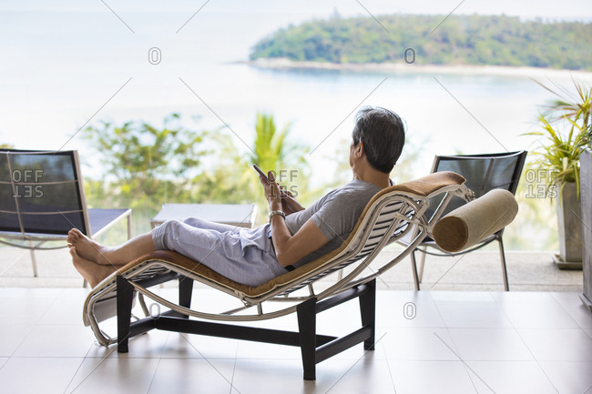 Happy senior Chinese man relaxing on balcony