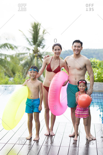 Happy young Chinese family with swimming tubes