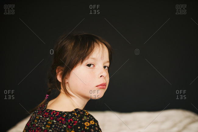 Unhappy young girl sitting on bed looking over shoulder