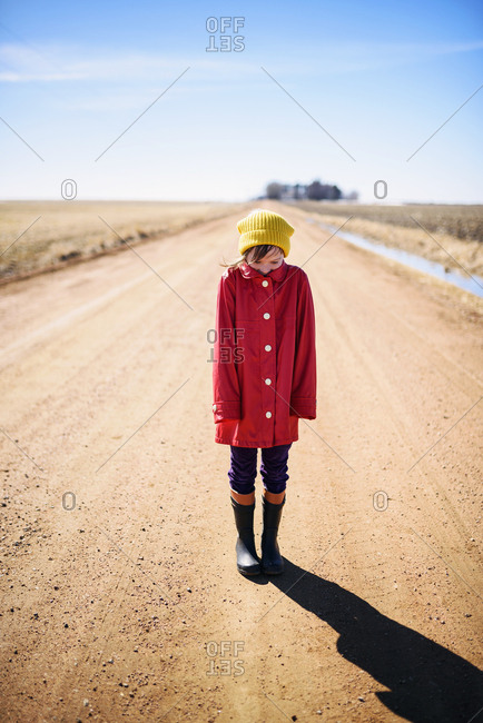 Young girl with chin tucked into collar of coat standing on deserted country road