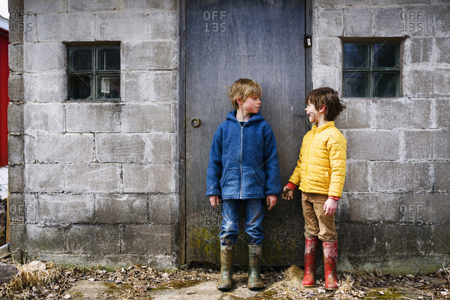 Two young boys grubby from playing in the mud talking to each other outside shed