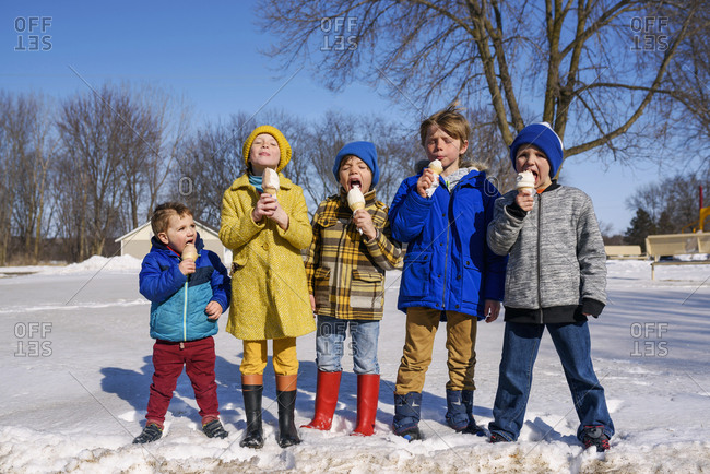 Five children standing side by side eating ice cream in the snow