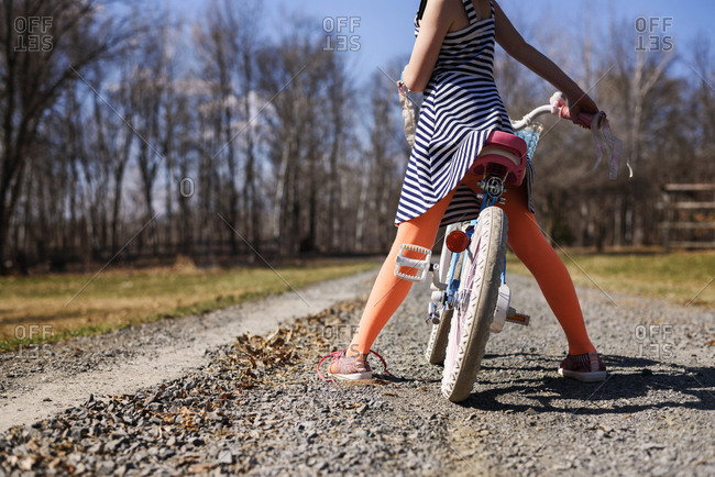 Lower view of girl stopped on bike in country
