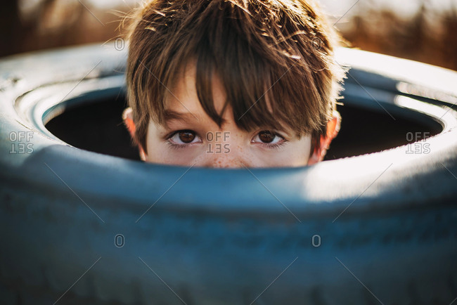 Portrait of young boy peeking out of a tire swing