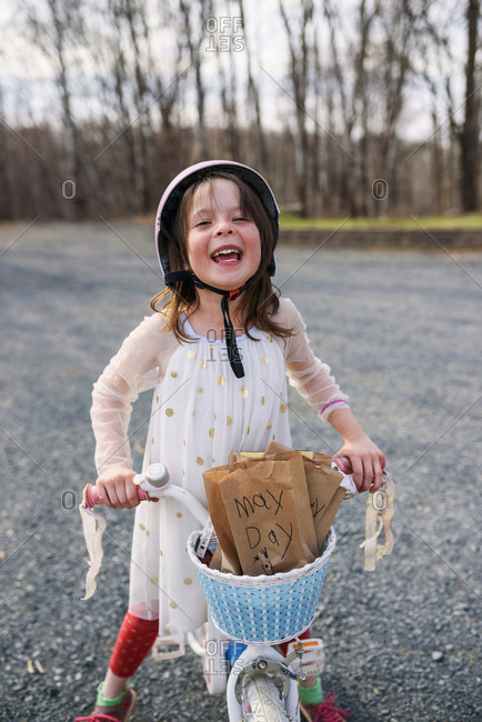 Excited girl delivering May Day packages on bike