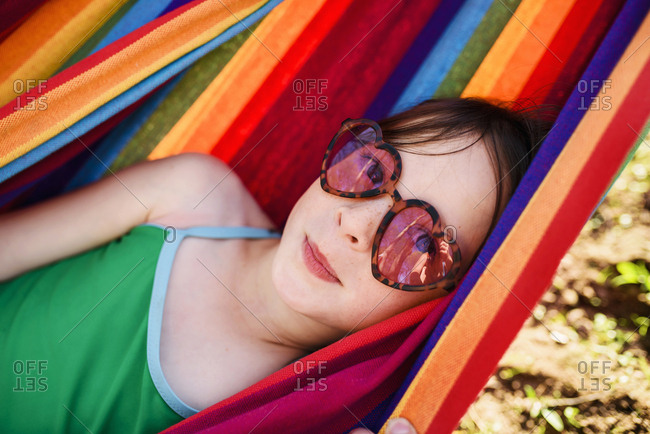 Young girl in heart-shaped sunglasses relaxing in a colorful hammock