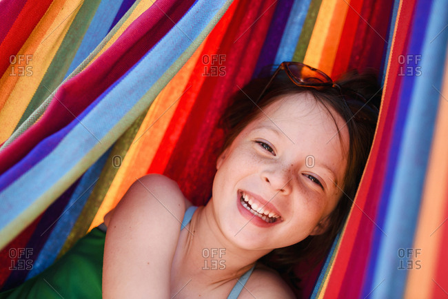 Freckled girl smiling in striped hammock on sunny day