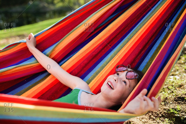 Little girl stretching out in striped multicolor hammock