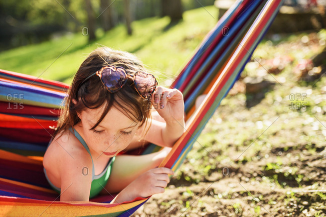 Young brunette girl looking over edge of hammock to the ground