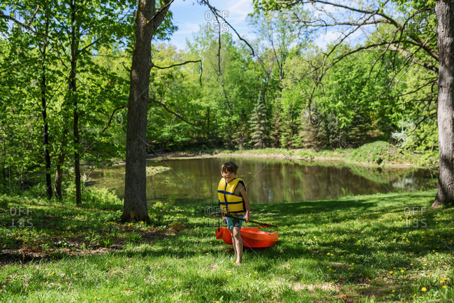 Young boy carrying a kayak in the forest