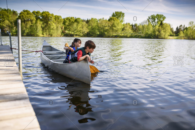 Two young kids sitting in a canoe trying to catch fish