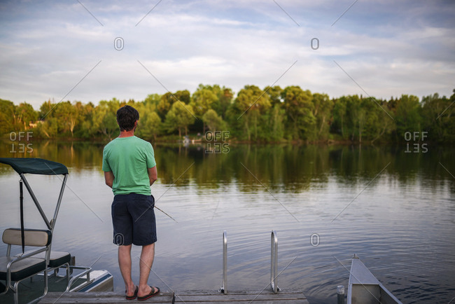 Man fishing alone on wooden dock