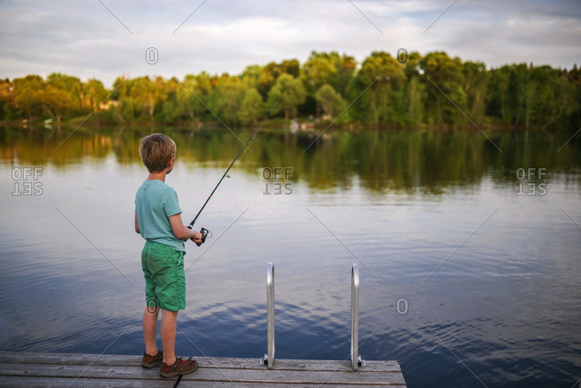 A young boy fishing alone off a dock