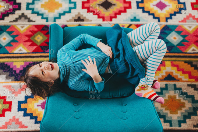 Overhead view of young girl on chair over brightly colored rug