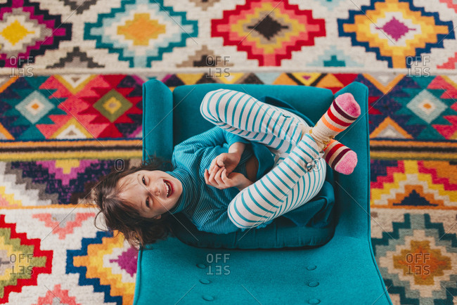 Top view of young girl playing in upholstered chair over vibrant patterned carpet