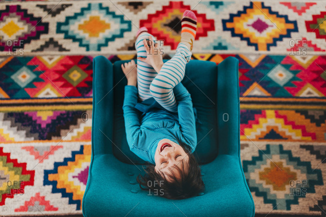 Upside down top view of excited brunette girl sitting in chair