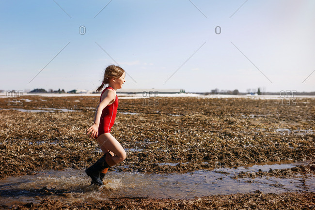 A young girl playing in a mud puddle in a field