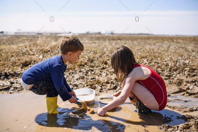 Two young kids playing in mud puddles in a field